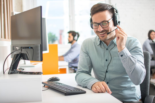 Friendly customer support agent man with headset talking with client in call centre