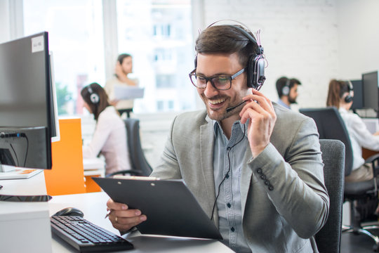 Male technical support worker with headset reading something from clipboard while talking with a client in call center