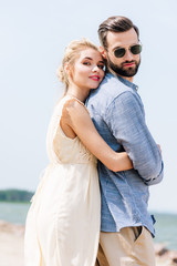 low angle view of happy blonde woman hugging bearded boyfriend at beach