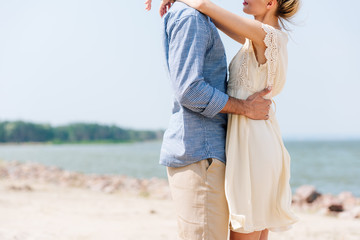 cropped view of romantic couple hugging at beach