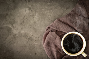 Hot cup of a black coffee with morning light affect to smoky aroma on napkin, old cement floor.  Top view, copy space. Wall mural
