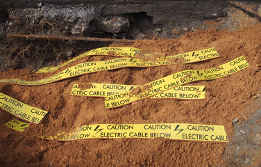 yellow tape signs warning of buried electric cable below in a trench being excavated during roadwork and building construction
