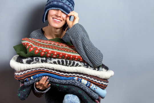 Young woman hold pile of sweaters wearing knitted hat and warm wool sweater