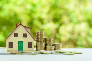 Property investment / reverse mortgage, financial concept : Small home or house model with green door and stacks of rising coins, depicts saving money to buy a new residential asset, human basic needs