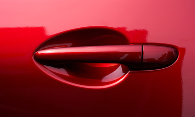 Close up of the door handle of a red car