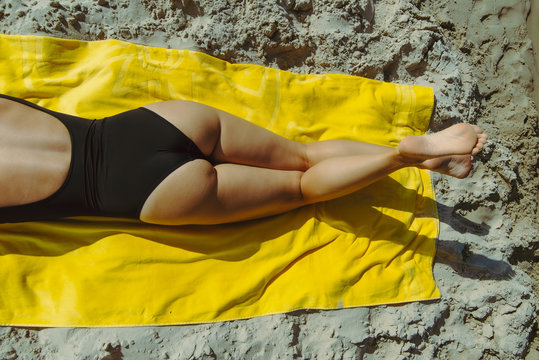 woman sunbathing at sand beach laying on yellow blanket