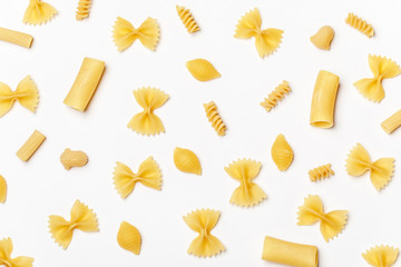 Various uncooked pasta on white background. Top view. Raw pasta with ingredients for cooking. Food concept
