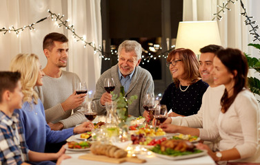 celebration, holidays and people concept - happy family having dinner party, drinking red wine and toasting at home
