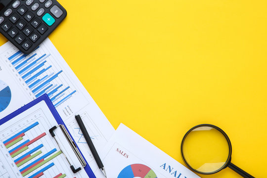 Financial papers with calculator, pen and magnifying glass on yellow background