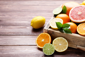 Citrus fruits in crate on wooden table