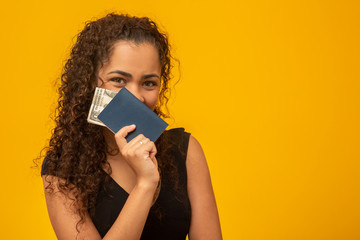 Beautiful young woman with curly hair holding a passport and money, thinking of her next trip. On yellow background
