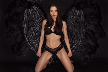 Sexy beautiful woman in lingerie and angel black wings. Wall mural