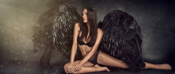 Sexy beautiful woman in lingerie and angel black wings.