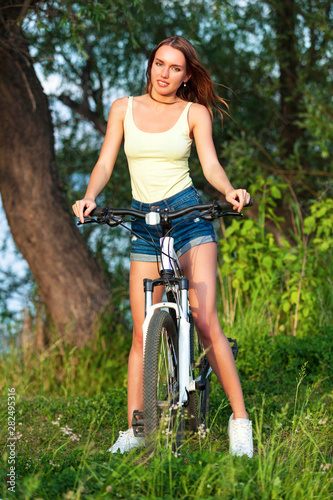 Happy Pretty Young Woman With Bicycle In A Summer Park