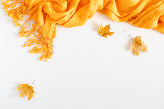Autumn cozy composition. Dried autumn leaves, yellow scarf on white background. Fall relax concept. Flat lay, top view, copy space