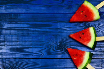 Watermelon slice popsicles with ice cream stick on blue wooden background. summer fruit background.