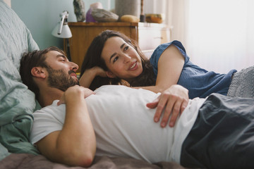 Couple relaxing and talking on bed