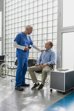 Male doctor talking to, comforting patient in clinic waiting room