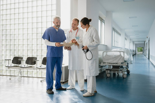 Doctors discussing medical record in hospital corridor