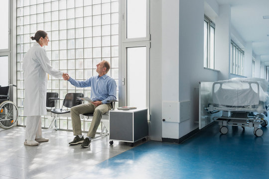 Doctor greeting, shaking hands with patient in hospital waiting room