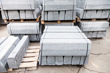 stockpiles of new gray concrete curbs