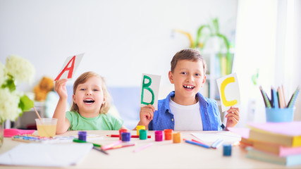 a little girl and a boy learn at home. happy kids at the table with school supplies smiling funny...