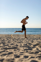 Bare chested man jogging on the beach