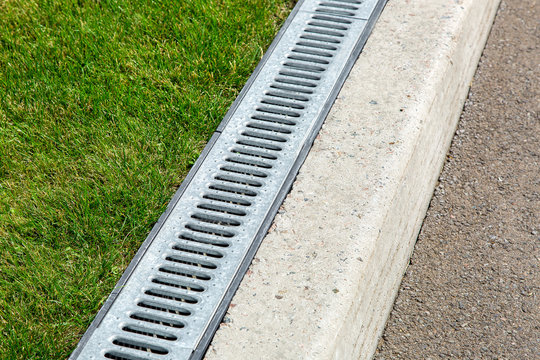 iron drainage system, closeup of an iron grille along a asphalt road and green grass.
