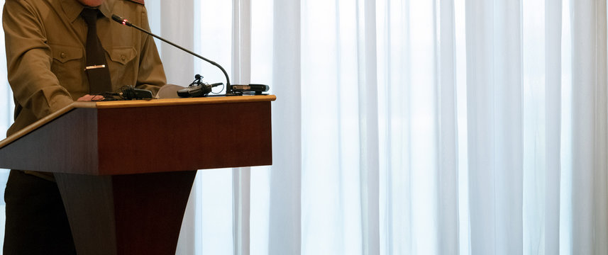 Abstract man in a green shirt stands on the podium in front of a microphone. Close-up. Copy space. Concept speech of a military official, the Minister of Defense or emergency situations.