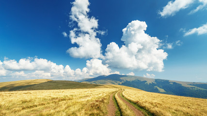 Highland ground road going away over horizon in the white clouds at blue sky background. Ukrainian Carpathian mountains location, Svydovets mountain ridge. Yellow and Blue - National colors of Ukraine