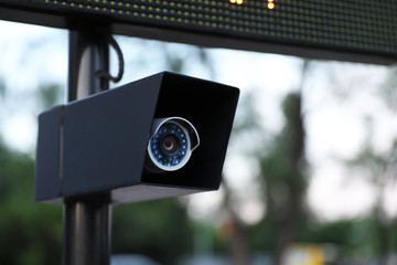 Modern CCTV security camera on street, closeup. Space for text