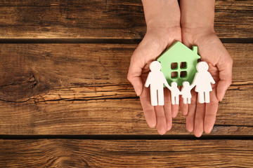 Woman holding figures of family and green house in hands on wooden background, top view. Space for text