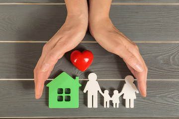 Woman holding hands near figures of house, red heart and family on grey wooden background, top view