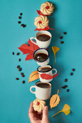 Balancing tower of splashing coffee cups, cookies and autumn leaves