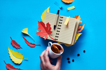 Open blank notebook with autumn leaves and hand with coffee on blue