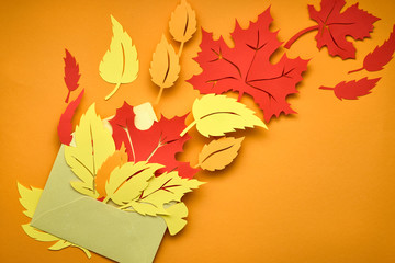 Flat lay on dark with red and orange paper leaves in envelope