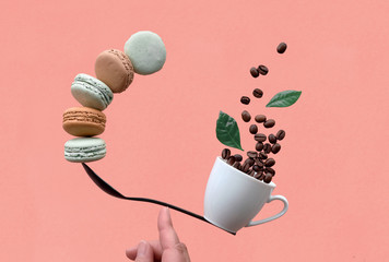 Balancing cup of coffee and macarons on a spoon on coral background