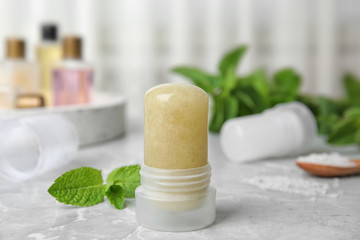 Natural crystal alum deodorant and mint on light grey marble table