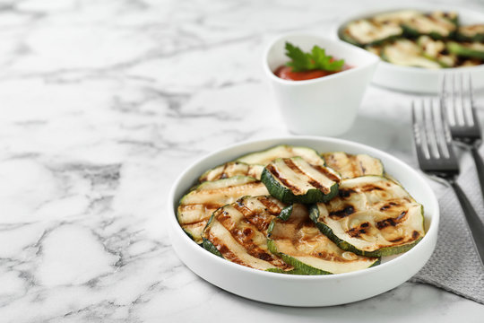 Grilled zucchini slices served on white marble table. Space for text