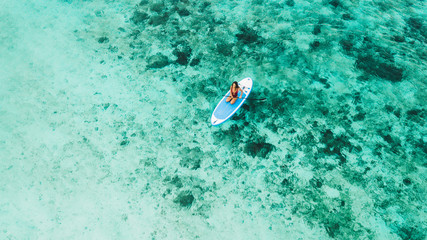 Woman sitting on sup board and enjoying turquoise transparent water and coral reef. Tropical travel, wanderlust and water activity concept.