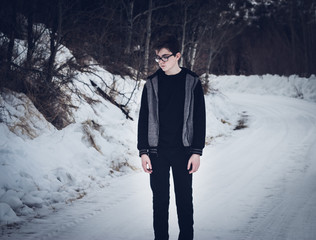 Teen Boy Standing on a Snow-Covered Road Looking Sad