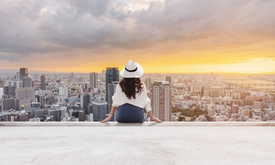 Wall Mural - Woman in white hat and clothes sitting on rooftop floor, looking at Osaka city in sunset