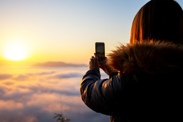 Woman use mobile take photo landscape sunrise and foggy on the hill