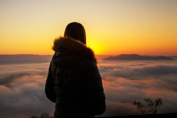 The back of the woman wearing a coat is watching the sunrise on the fog.
