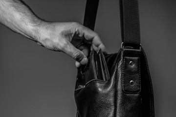 Black and white photo of a thief's hand pulling a purse from a leather bag on a gray background