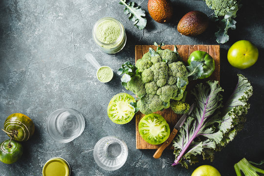 Healthy Organic green vegetables and jar with green powder for making smoothies.
