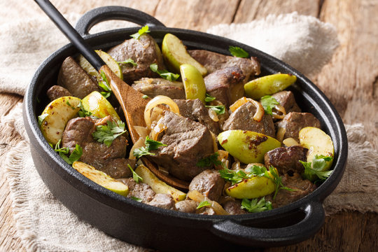 Spicy fried beef liver with green apples, onions and herbs close-up in a pan on the table. horizontal