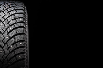 New winter studded tire, safety and premium quality. black background, close-up
