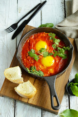 fried eggs in a pan with tomato sauce, shakshuka