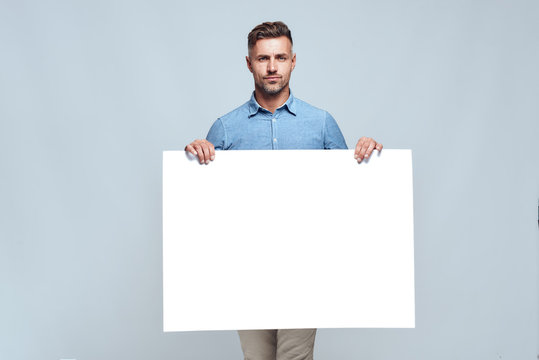 Your text here. Portrait of handsome bearded man in casual clothes holding empty blank board and looking at camera while standing against grey background